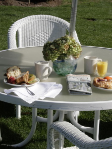 Breakfast outside on a glass table with wicker chairs